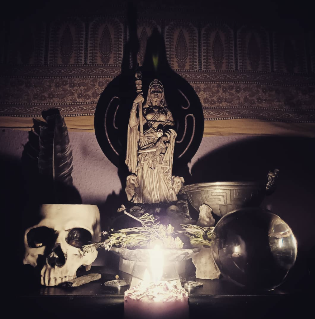An altar image with a statue of Hekate, a skull, a crystal ball and some offerings.